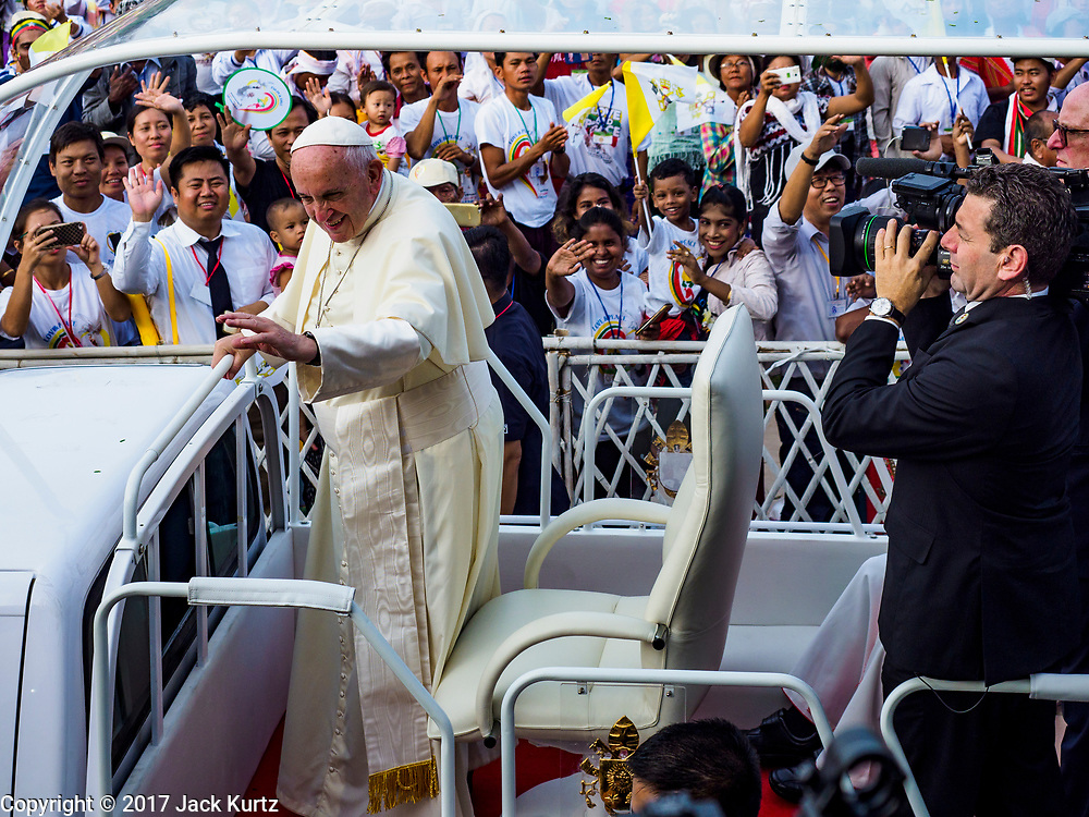 """29 NOVEMBER 2017 - YANGON, MYANMAR:  POPE FRANCIS, standing in the """"Popemobile,"""" drives through the crowd at the Papal Mass in Yangon. Hundreds of thousands of Catholics from Myanmar attended the mass said by Pope Francis at Kyaikkasan Sports Ground in Yangon Wednesday. Pope Francis is on the first visit by a Pope to Myanmar.   PHOTO BY JACK KURTZ"""