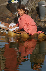 A displaced Indian girl who fled her village near the border  region of Pallanwala in June 1999 washes clothes in a camp near Akhnur, India.  (Photo by Ami Vitale/Getty Images)
