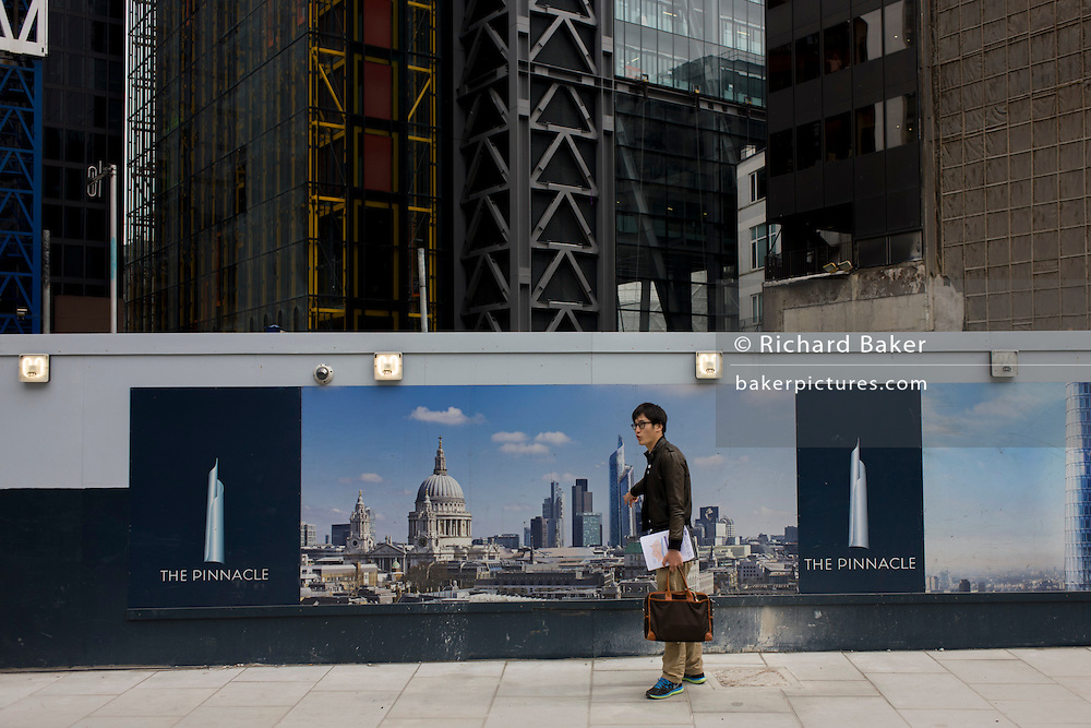 Asian man points to future skyscraper on construction landscape showing City of London cityscape on hoarding