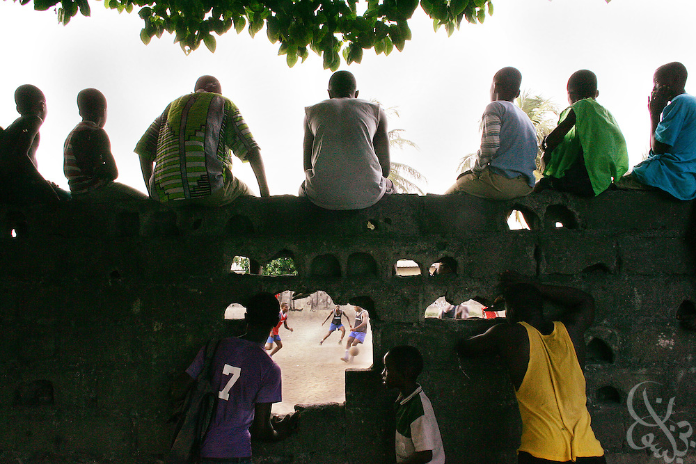 """Supporters watch through a hole in a wall as the """"Almighties of Koomassi"""" academy football club practices in the Koomassi neighborhood of Abidjan, Ivory Coast February 17, 2006.  Trying to mimic the successes of ASEC academy, more than 300 rival football academies have been started in Abidjan. Parents hoping of their children will become national team members or pro european league players often become indebted in order to put their children into the copycat academies, which focus on football skills, but do little to educate the young Ivorians who attend them.   ."""
