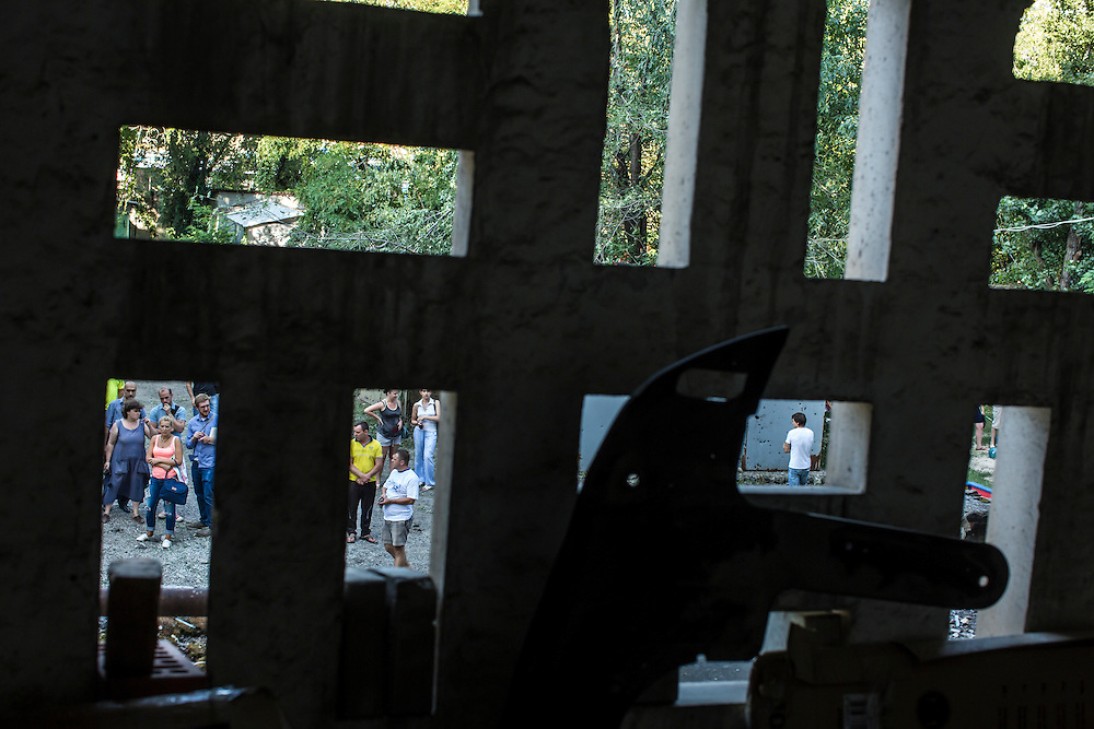 Local residents and journalists gather outside an apartment building hit by a suspected grad rocket strike on Tuesday, July 29, 2014 in Donetsk, Ukraine.