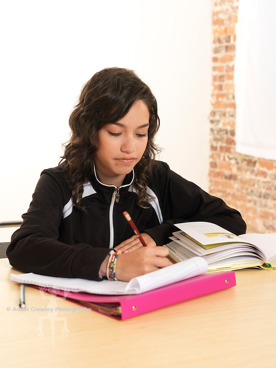 Hispanic girl (14 years old) at desk with schoolwork.