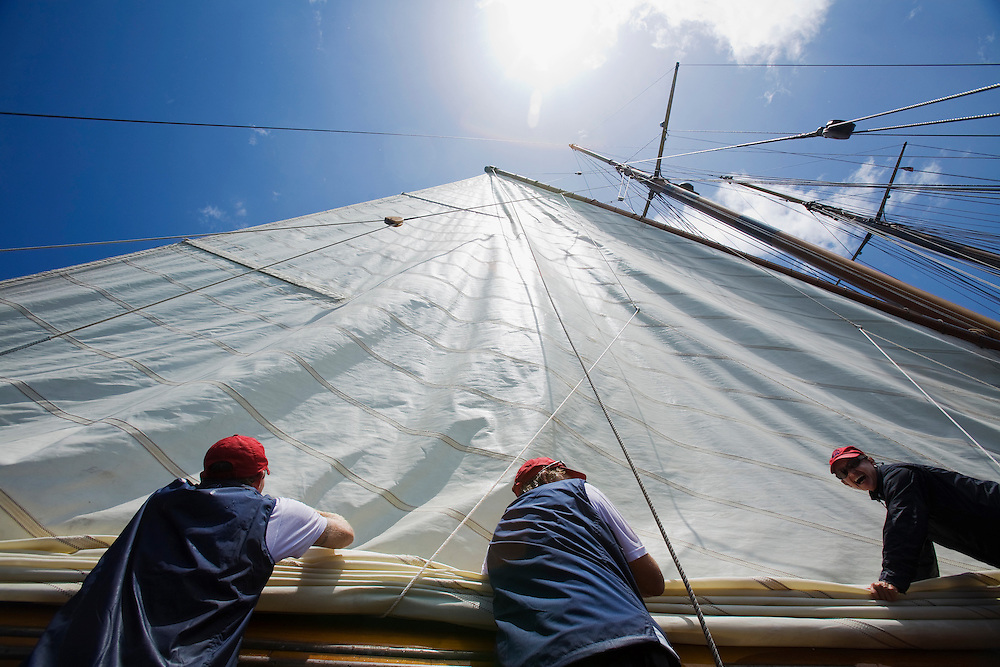 A female crew member laughs at the camera while she helps to stow the gaff rigged mizzen sail of the schooner yacht SY Altair during the 2008 Antigua Classic Yacht Regatta . This race is one of the worlds most prestigious traditional yacht races. It takes place annually off the cost of Antigua in the British West Indies. Antigua is a yachting haven, historically a British navy base in the times of Nelson.