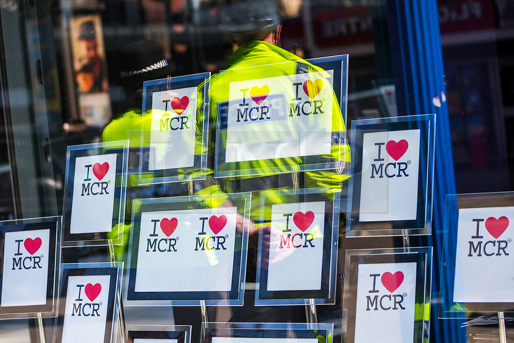 © Licensed to London News Pictures. 22/05/2018. Manchester UK. Picture shows the reflection of two police officers in Manchester this morning as the city marks the first anniversary of the Manchester Arena bombing. 22 people died when Salman Abedi detonated a bomb at an Ariana Grande concert. Photo credit: Andrew McCaren/LNP