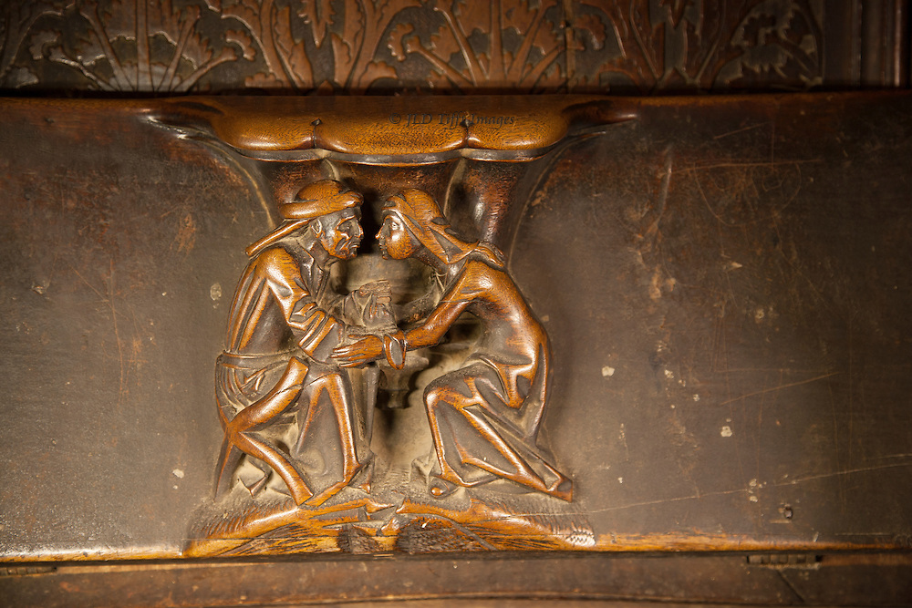 Misericord in Toledo Cathedral, showing man and woman seated opposite each other, the man looking miserable and the woman seeming to offer comfort with an extended arm and hand.