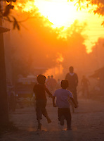 Two boys running on a street at sunset, Nepalganj, Nepal