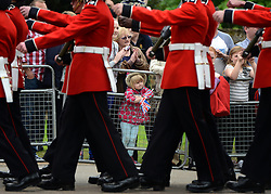 © Licensed to London News Pictures. 19/05/2012. WIndsor, UK A little girl watches Troops march through Windsor. Armed Forces muster and parade in Windsor today , 19th May 2012, in tribute to Her Majesty the Queen for the Diamond Jubilee. 2,500 troops paraded through the town before the Queen and Duke of Edinburgh to mark the Diamond Jubilee. Once the parade has passed the Queen and Duke traveled along the same route to an arena within Home Park, where the troops mustered. A tri-service flypast of 78 aircraft, including helicopters, Hawks, the Battle of Britain Memorial Flight, the Red Arrows and Tornados went overhead. Photo credit : Stephen Simpson/LNP