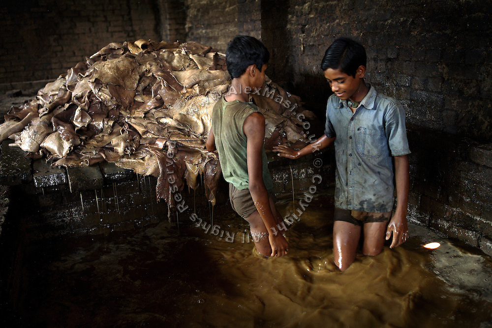 Two children are using their feet to find the remaining skins in a bath during the process of liming, the removal of hair and impurities with the use of water and various agents, in an illegal tannery unit inside Jajmau, Kanpur, Uttar Pradesh. Children are largely employed to work on scraps, or little pieces of skin, like the head and the ears of the animal, which will become a small bag, a wallet, or maybe a cheap phone leather case.