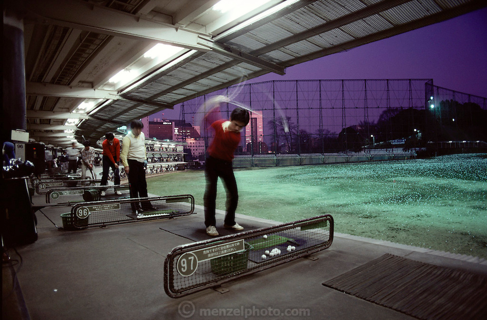 Multi-story golf driving range in Tokyo, Japan, at dusk.