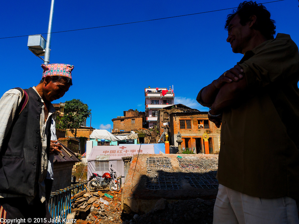 03 AUGUST 2015 - SANKHU, NEPAL: People walk past a Hindu temple destroyed in the Nepal earthquake in Sankhu, a community about 90 minutes from central Kathmandu. The Nepal Earthquake on April 25, 2015, (also known as the Gorkha earthquake) killed more than 9,000 people and injured more than 23,000. It had a magnitude of 7.8. The epicenter was east of the district of Lamjung, and its hypocenter was at a depth of approximately 15 km (9.3 mi). It was the worst natural disaster to strike Nepal since the 1934 Nepal–Bihar earthquake. The earthquake triggered an avalanche on Mount Everest, killing at least 19. The earthquake also set off an avalanche in the Langtang valley, where 250 people were reported missing. Hundreds of thousands of people were made homeless with entire villages flattened across many districts of the country. Centuries-old buildings were destroyed at UNESCO World Heritage sites in the Kathmandu Valley, including some at the Kathmandu Durbar Square, the Patan Durbar Squar, the Bhaktapur Durbar Square, the Changu Narayan Temple and the Swayambhunath Stupa. Geophysicists and other experts had warned for decades that Nepal was vulnerable to a deadly earthquake, particularly because of its geology, urbanization, and architecture.    PHOTO BY JACK KURTZ