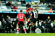 Ryan Bertrand (#21) of Southampton challenges Andy Carroll (#7) of Newcastle United in the air during the Premier League match between Newcastle United and Southampton at St. James's Park, Newcastle, England on 8 December 2019.