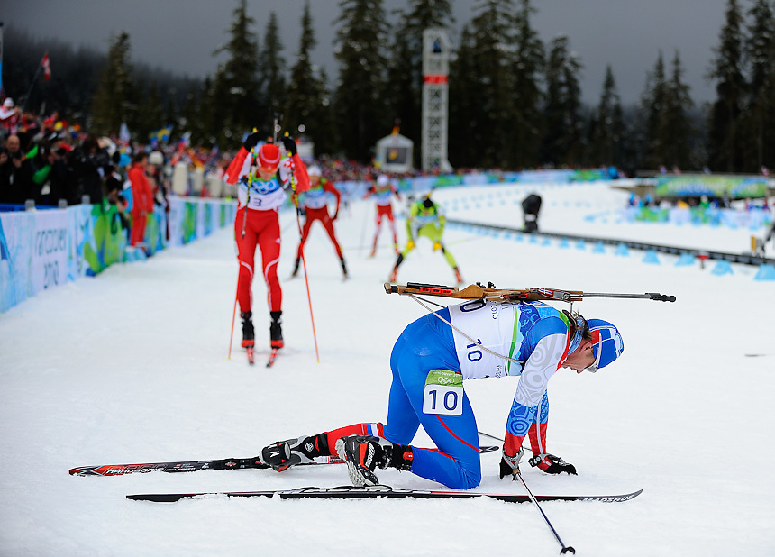Russian Federation's Ivan Tcherezov (foreground) collapses in exhaqustion after the men's biathlon 12.5 km pursuit at Whistler Olympic Park on day 5 of the Vancouver 2010 Olympic Winter Games.