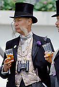 Racegoer, with traditional monocle eyeglass, drinking Pimms fruit punch by the Grandstand at Epsom Racecourse on Derby Day, UK