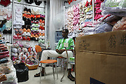 31 July 2007 - Guangzhou, China - Assiongbon Kankoe, 28, from Ghana sits in the underwear shop that he regularly buys goods from to send back to Ghana. He has been coming to Guangzhou for several years and is one of the more successful traders. By some estimates over 10,000 Africans from many different nations live and pass through Guangzhou which has overtaken Hong Kong as the new hub for African businessmen looking to cut out the middle man. Some come for a few weeks, others years. These African traders, most of whom come from West African nations like Ghana, Togo and Nigeria, profit by purchasing cheap goods direct from Chinese factories and then sending them back to their home countries where they can be sold at higher prices. Photo Credit: Luke Duggleby
