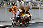 Thonglor (Sukhumvit Soi 55), at this time Bangkok's most fashionable area. Street vendor on a bicycle selling brooms.