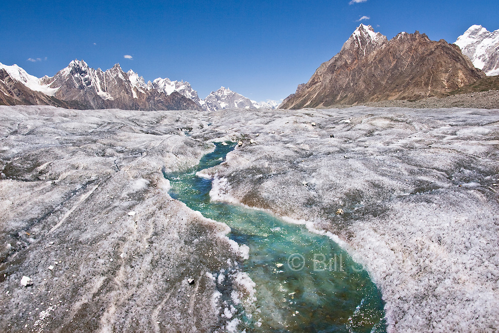 A frozen stream running on the surface of glacial ice surrounded by the Karakoram himalaya mountains on the Biafo Glacier in Pakistan