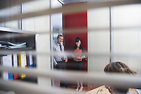 Business colleagues talking in office seen through window blinds