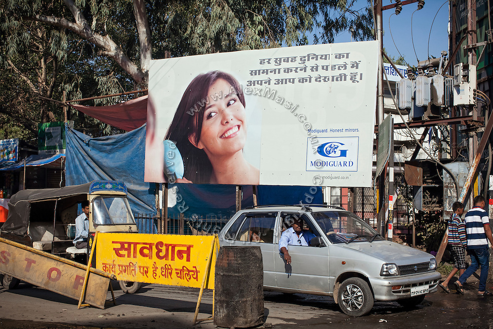 Cars are passing by a advertisement about mirrors, on the road of Bhopal, Madhya Pradesh, India, city of the infamous '1984 Gas Disaster', a tragic event that today continues to consume people's lives.