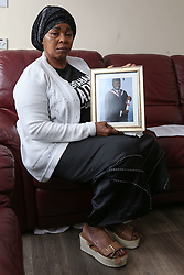 Ronke Badru, mother of Abraham Badru holds a picture of her son in her sitting room. Abraham Badru, a personal trainer, 26, was shot in the chest on 25th March in Ferncliff Road, E8. He received a National Police Bravery Award after intervening in a rape and giving evidence in court. London, April 25 2018.