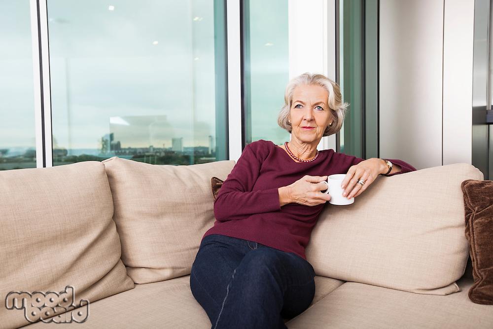 Senior woman with coffee mug sitting on sofa at home