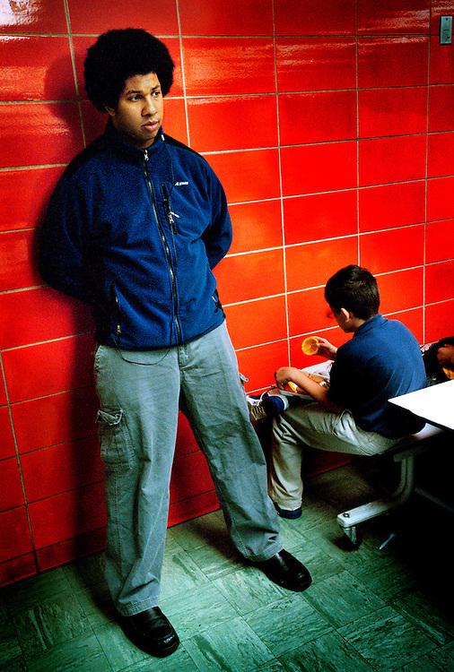 USA, New York, Bronx, 23 March 2005.The KIPP - Knowledge Is Power Program - is a network of schools in under-resourced communities in the United States. The schools are public but kids have to agree to spend 10 hours a day at school six days a week, and to keep to a high discipline. The KIPP was started by two motivated teachers and has proven to be extremely successful with a lot of students continuing on to college..The KIPP Academy in The Bronx ranks in the top 10% of all New York City Public Schools. It also has an orchestra where all the students play..The principal, Quinton Vance, is watching a student who was punished for misbehaving. The punishment consists in having to eat his lunch apart from the others, facing the wall.<br /> <br /> <br /> Etats-Unis, New York, Bronx, 23 mars 2005.Le KIPP (Knowledge is Power Program, en franc?ais, Programme Le Savoir est le Pouvoir), est un re?seau d'e?coles destine?es aux communaute?s de?favorise?es des Etats-Unis. Les e?coles sont publiques mais les enfants doivent accepter de venir a? l'e?cole 10 heures par jour six jours par semaine et se conformer a? une discipline stricte. Le KIPP a e?te? cre?e? par deux enseignants motive?s et a beaucoup de succe?s, une grande partie des e?le?ves poursuivant des e?tudes supe?rieures..La KIPP Academy du Bronx fait partie des 10% d'e?coles les plus co?te?es parmi les e?coles publiques de New York. Les e?le?ves font tous partie de l'orchestre de l'e?cole..Le proviseur, Quinton Vance, surveille un e?le?ve qui a e?te? puni pour mauvaise conduite. La punition consiste a? manger tout seul face au mur...&copy; Chris Maluszynski /MOMENT