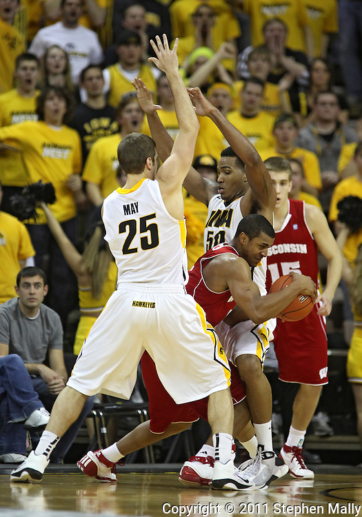 February 09 2011: Wisconsin Badgers guard Jordan Taylor (11) tries to get away from Iowa Hawkeyes guard/forward Eric May (25) and Iowa Hawkeyes forward Jarryd Cole (50) during the second half of an NCAA college basketball game at Carver-Hawkeye Arena in Iowa City, Iowa on February 9, 2011. Wisconsin defeated Iowa 62-59.