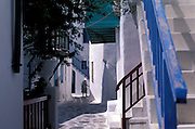 An elderly lady walks through a narrow lane of Mykonos Old Town.