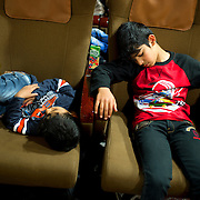 Greece with Doctors of the World (Medecins du monde). Hellenic Seaways ferry from Lesvos to Chios to Athens, taken by refugees. Doctors of the World have a clinic on board with a doctor, nurse, interpreters and social workers. Two exhausted young boys fall asleep as soon as they get  on board.