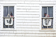 Patriotic stars and stripes flags and dog and hen portraits in windows of wood shingle house at Cape Cod, New England, USA
