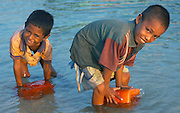 Two young boys collect water, Papagaran island, Komodo National Park