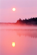 Reflection of sunrise on Childs Lake with pink fog<br />Duck Mountain Provincial Park<br />Manitoba<br />Canada