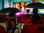 "30 JUNE 2016 - BANGKOK, THAILAND: Women watch a Chinese opera performance at Chiao Eng Piao Shrine in Bangkok. Chinese opera was once very popular in Thailand, where it is called ""Ngiew."" It is usually performed in the Teochew language. Millions of Chinese emigrated to Thailand (then Siam) in the 18th and 19th centuries and brought their culture with them. Recently the popularity of ngiew has faded as people turn to performances of opera on DVD or movies. There are about 30 Chinese opera troupes left in Bangkok and its environs. They are especially busy during Chinese New Year and Chinese holidays when they travel from Chinese temple to Chinese temple performing on stages they put up in streets near the temple, sometimes sleeping on hammocks they sling under their stage.       PHOTO BY JACK KURTZ"
