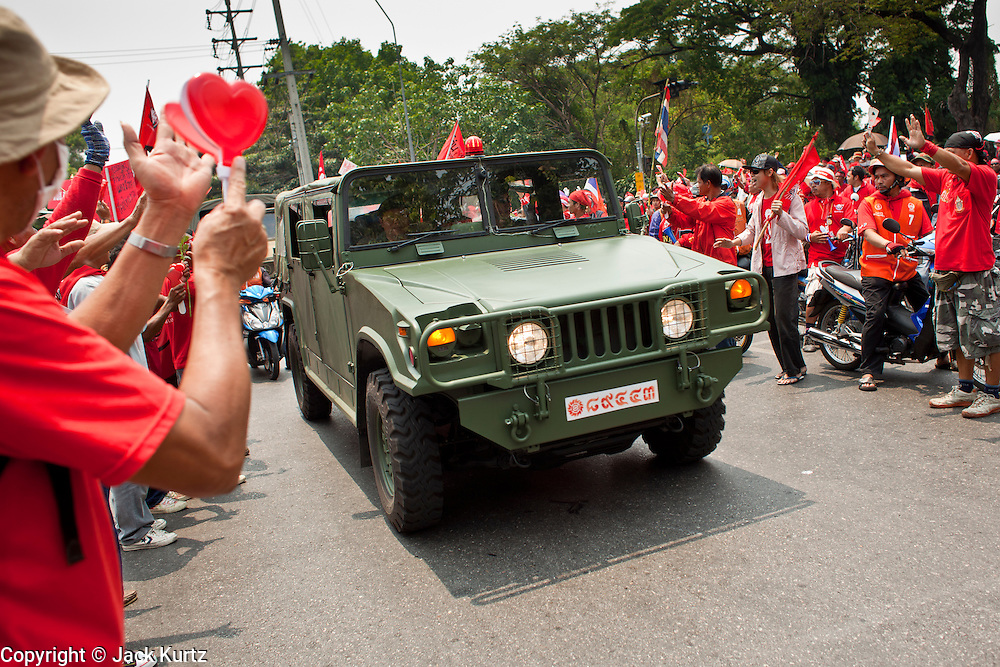 "Mar. 27, 2010 - BANGKOK, THAILAND:  Red Shirt demonstrators cheer as Thai soldiers travel in a convoy through their march. The Thai soldiers were supposed to keep order but many cheered the Red Shirts and others accepted flowers from them. More than 80,000 members of the United Front of Democracy Against Dictatorship (UDD), also known as the ""Red Shirts"" and their supporters marched through central Bangkok March 27 during a series of protests against and demand the resignation of current Thai Prime Minister Abhisit Vejjajiva and his government. The protest is a continuation of protests the Red Shirts have been holding across Thailand. They support former Prime Minister Thaksin Shinawatra, who was deposed in a coup in 2006 and went into exile rather than go to prison after being convicted on corruption charges. Thaksin is still enormously popular in rural Thailand.    PHOTO BY JACK KURTZ"
