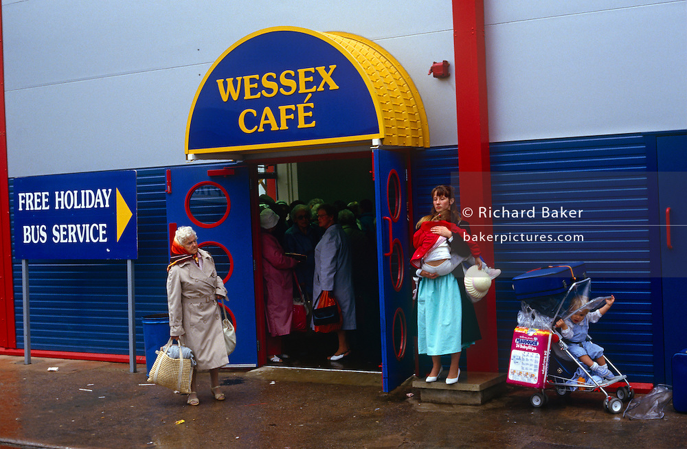 Holidaymakers shelter from typical summer rain during their stay at the regenerated Butlins holiday centre at Minehead.