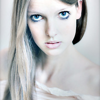 Close up of young girl with large blue eyes and long blonde hair looking at camera