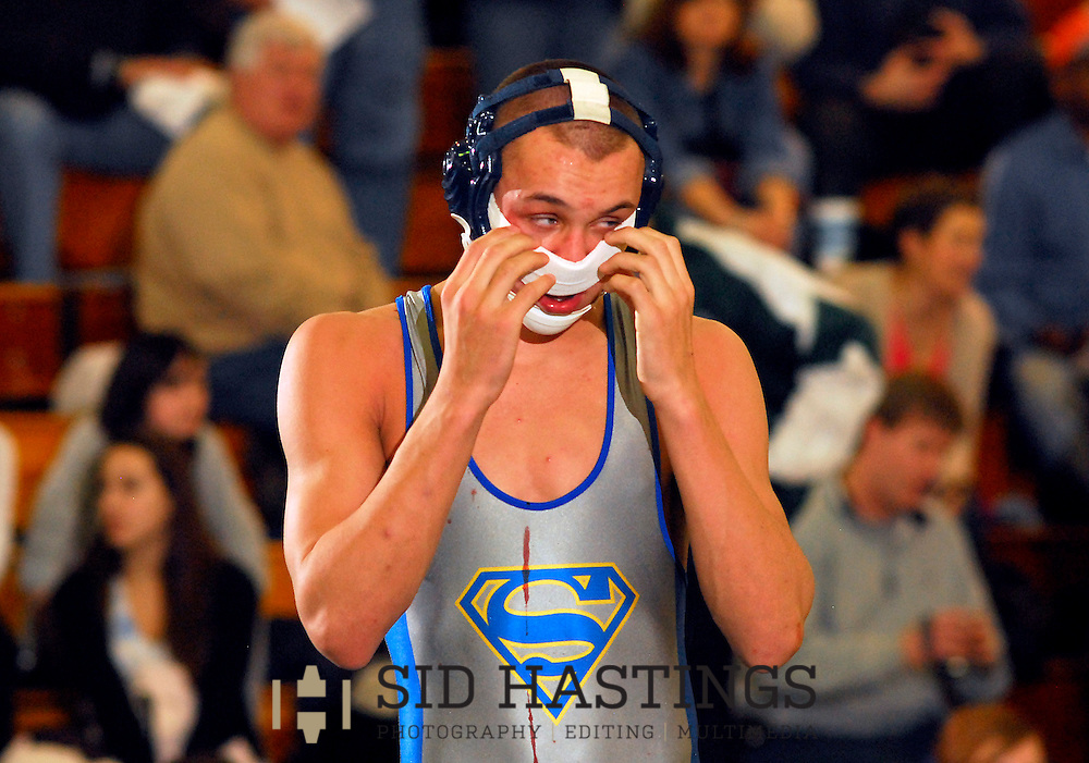 13 FEB. 2010 -- ST. LOUIS -- Seckman High School wrestler Corey Matt adjusts a wrap applied by trainers to help control his bloody nose during his 152-pound match with Eureka's Gary Hahn at the MSHSAA Class 4 District 1 wrestling tournament at Lindbergh High School in St. Louis Saturday, Feb. 13, 2010. Photo (c) copyright by Sid Hastings.