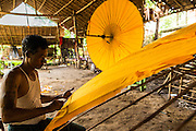 14 JUNE 2013 -  PATHEIN, AYEYARWADY, MYANMAR: A worker glues the cover on an umbrella ordered by a restaurant in Germany at the Shwe Sar umbrella factory in Pathein. Pathein is a center of the Burmese umbrella and parasol industry. Most are actually parasols made in the traditional Burmese way using treated paper which is not water proof. Shwe Sar's umbrella's are made with treated cloth and are waterproof. Since US and European sanctions have been lifted businesses in Myanmar have seen an explosion in exports. Shwe Sar exports most of their umbrellas to Europe. Pathein, sometimes also called Bassein, is a port city and the capital of the Ayeyarwady Region, Burma. It lies on the Pathein River (Bassein), which is a western branch of the Irrawaddy River. It's the fourth largest city in Myanmar (Burma) about 190 km west of Yangon.   PHOTO BY JACK KURTZ