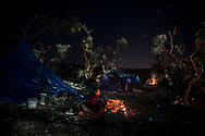 An Afghan boy tries to warm up next to a bonfire at night in Moria village on the northeastern Greek island of Lesbos, Tuesday, Nov. 17, 2015. European leaders pressed ahead with efforts to discourage people from heading to Europe to find work and kept seeking ways to send back home thousands who don't qualify for asylum. (AP Photo/Santi Palacios)