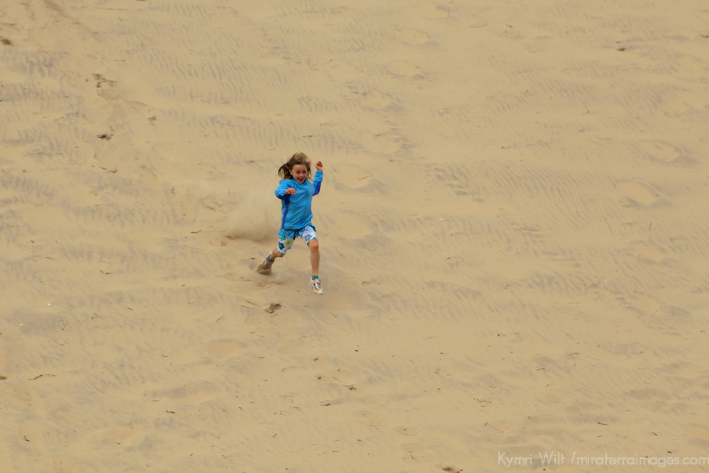 Europe, Ireland, Brittas Bay. Girl running down dune at Brittas Bay.