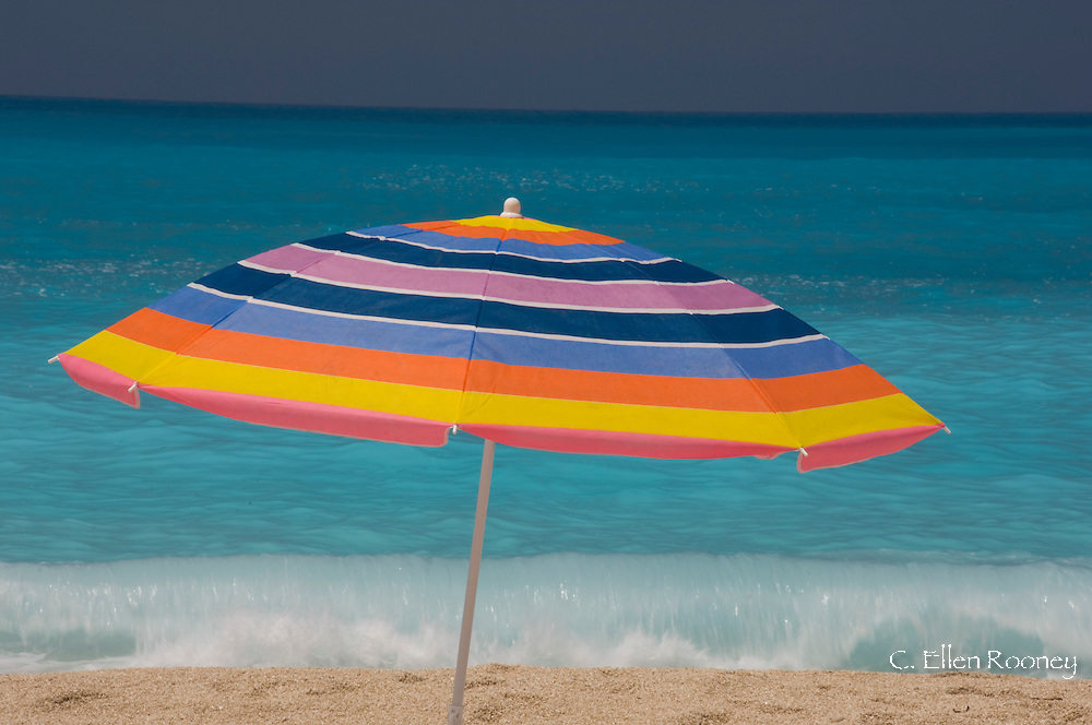 A colourful beach umbrella near the sea on Myrtos Beach.  Kefalonia, The Ionian Islands, Greece