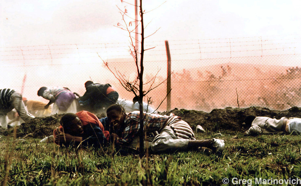 IPMG0049 South Africa, Bisho 1992..ANC supporters flee towrads the South African side of the border with the aprtheid homeland of Ciskei after they were fired on and 29 marchers who were killed and dozens more wounded  - some inside South Africa, September 7, 1992 after an ANC march on the Ciskei homeland.  The ANC supporters were killed when Ciskei security forces opened fire after the marchers broke through the border in an attempt to march on aforce the Ciskeien military leader Brigadier Oupa Gqozo to allow free political activity in Ciskei. .Photograph by Greg Marinovich/South Photographs