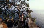 Boys collect the offerings left the day before from the tree that overlooks the ocean.<br /> Tirukoneswaram Temple.
