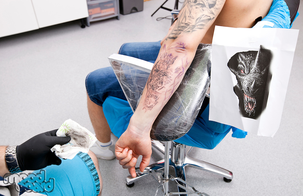 Artist tattooing man's arm in tattoo parlor
