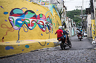 Taxi bikes take customers up the steep hill of the Santo Amaro favela, Rio de Janeiro, Brazil. The trip costs 2.50 Brazilian reias, about 80p one way. According to Patrick Ashcroft an English (Stockport) researcher and teacher who lives in the favela, it is fairly quiet and non violent. There is a heavily armed police presence in the favela.<br /> Picture by Andrew Tobin/Focus Images Ltd +44 7710 761829<br /> 20/06/2014