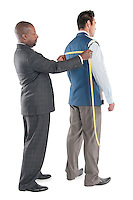 Man having back measured by tailor