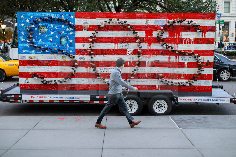 © Licensed to London News Pictures. 07/11/2016. New York CIty, USA. People walk past an artwork which features most memorable headlines of the presidential election in New York City on Monday, 7 November, the day before the presidential election day in the United States of America. Photo credit: Tolga Akmen/LNP