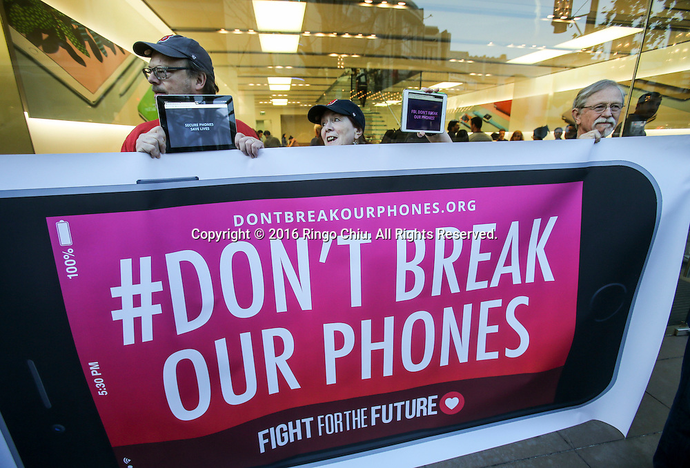 Demonstrators hold up signs  and iPads during a rally in support of data privacy outside the Apple store, Tuesday, Feb. 23, 2016, in Los Angeles. Protesters assembled in more than 30 cities around the world to lash out at the FBI for obtaining a court order that requires Apple to make it easier to unlock an encrypted iPhone used by a gunman in December's mass murders in California.(Photo by Ringo Chiu/PHOTOFORMULA.com)<br /> <br /> Usage Notes: This content is intended for editorial use only. For other uses, additional clearances may be required.