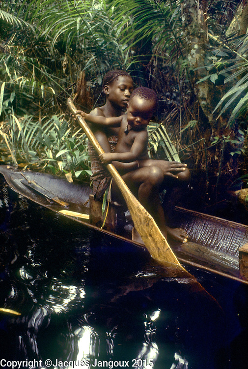 Africa, Democratic Republic of the Congo, Ngiri River islands area, Libinza tribe, girl with baby learning how to paddle in canoe in swamp forest.