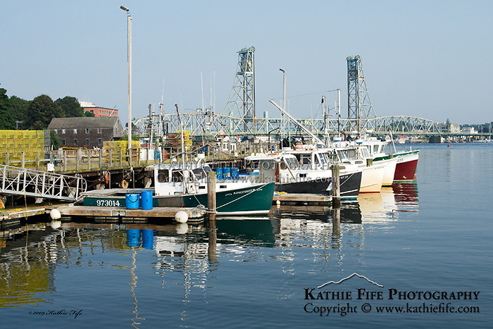 Historic Portsmouth Harbour, NH.  The state docks, fishing boats, and the Memorial Bridge in the background.<br />