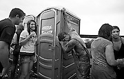 Waiting in line to use the portable toilets, festivals attendees mock and laugh at a young man already extremely intoxicated, covered in mud and missing the shirt he came with.